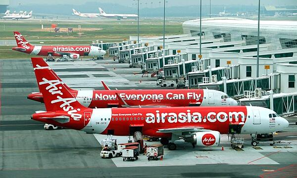 AirAsia planes at an airport, ready for boarding.