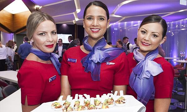 Three members of the Virgin Australia cabin crew serving canapés.